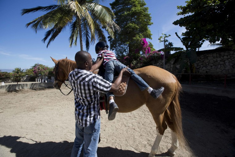 In this Jan. 7, 2017 photo, Judeley Hans Debel dismounts Tic Tac with some help from his teacher at the Chateaublond Equestrian Center in Petion-Ville, Haiti. Advocates of therapeutic riding say it improves balance, coordination and confidence with the movements of the horse mimicking pelvic motions involved in human walking. (AP Photo/Dieu Nalio Chery)