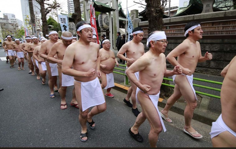 Japanese bathers run together outside Teppozu Inari Shinto Shrine before dipping in a cold water tub with blocks of ice during a winter ritual at the shrine in Tokyo, Sunday, Jan. 8, 2017. About 100 people gathered for the mid-winter event to pray for their healthy new year and displayed their perseverance. (AP Photo/Shizuo Kambayashi)