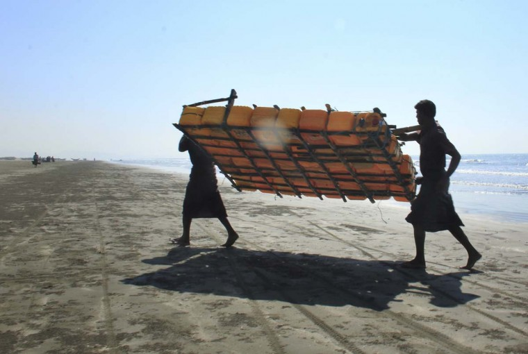 In this Jan. 16, 2017, photo, Rohingya fishermen carry a fishing raft, constructed with empty plastic containers, up the beach in Tha Pyay Taw village, Maungdaw, western Rakhine state, Myanmar. Their usual, sturdy fishing boats were outlawed three months ago when Myanmar authorities launched a sweeping and violent counter-insurgency campaign in Rakhine state, home to the long-persecuted Rohingya Muslim minority. The ban on fishing boats -- meant to prevent insurgents from entering or leaving the country by sea -- is just one small provision in the wider crackdown, in which authorities have been accused of widespread abuses. (AP Photo/Esther Htusan)