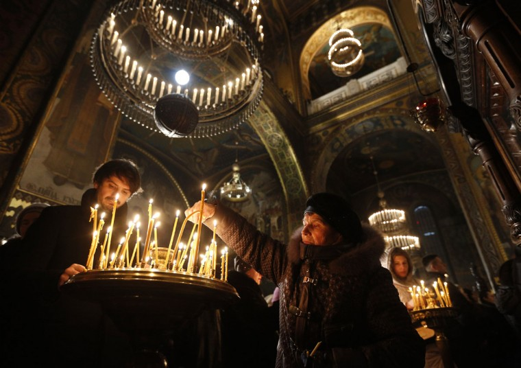 People light candles in a church to mark the Orthodox Christmas in the St. Volodymyr Cathedral in Kiev, Ukraine, Friday, Jan. 6, 2017. (AP Photo/Sergei Chuzavkov)