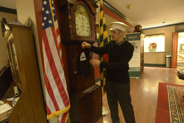 "Historian Steven Foote reveals one of the Admiral Fell's ""ghosts"" -- a Natty Boh-man in the lobby's grandfather clock. (Christina Tkacik/Baltimore Sun)"