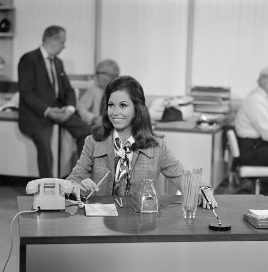 American actress Mary Tyler Moore (as Mary Richards) sits at her new desk and sharpens pencils in an electric sharpener after being hired in the newsroom of television station WJM in a scene from the 'Love Is All Around' episode of 'The Mary Tyler Moore Show' (also known as 'Mary Tyler Moore'), Los Angeles, California, July 30, 1970. The episode, the debut episode of the show, originally aired on September 15, 1970. (Photo by CBS Photo Archive/Getty Images)