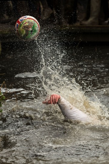 A competitor reaches for the ball during the annual Royal Shrovetide Football Match in Ashbourne, northern England, on February 28, 2017. The mass-participation ball game involves two teams, whose players are defined by which side of a small brook that bisects the town they were born, aiming to score a goal, which are some three miles apart. The game, which has very few rules, is played over two 8 hour periods on Shrove Tuesday and Ash Wednesday. Royal Shrovetide Football is believed to have been played annually in Ashbourne since 1667. (AFP PHOTO / Oli SCARFF)
