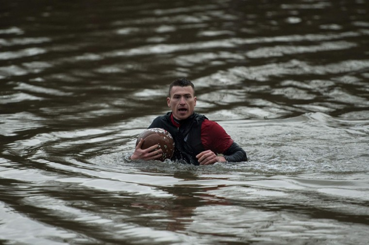 A competitor holds the ball during the annual Royal Shrovetide Football Match in Ashbourne, northern England, on February 28, 2017. The mass-participation ball game involves two teams, whose players are defined by which side of a small brook that bisects the town they were born, aiming to score a goal, which are some three miles apart. The game, which has very few rules, is played over two 8 hour periods on Shrove Tuesday and Ash Wednesday. Royal Shrovetide Football is believed to have been played annually in Ashbourne since 1667. (AFP PHOTO / OLI SCARFF)