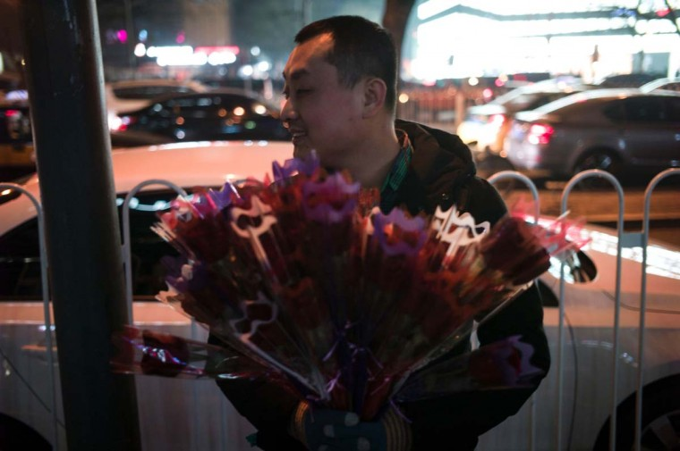 A vendor holds a bunch of flowers to sell on the street on Valentine's Day in Beijing on February 14, 2017. (FRED DUFOUR/AFP/Getty Images)
