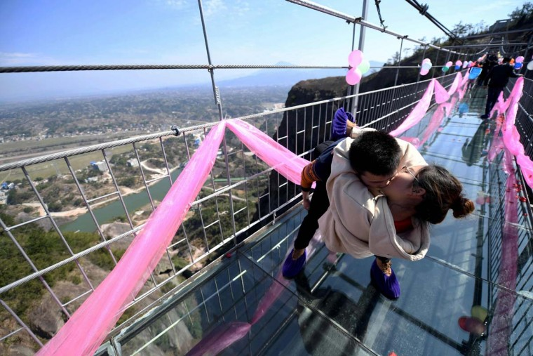 A Chinese couple kiss as they stand on a glass bridge during a kissing contest on Valentine's Day in Pingjiang, central China's Hunan province on February 14, 2017. (AFP/Getty Images)