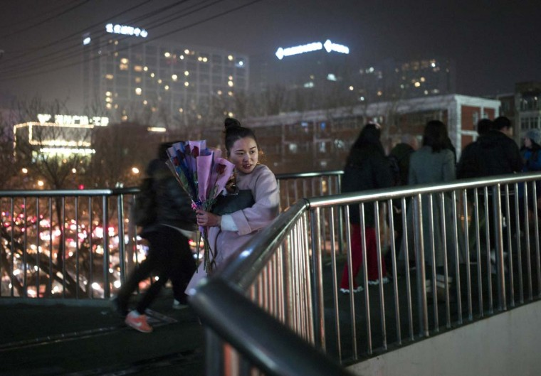 A woman holds flowers as she stands on a footbridge during Valentine's Day on a street in Beijing on February 14, 2017. A Pakistani court has banned public celebrations of Valentine's Day in the capital Islamabad while Indonesian students plan to spurn the event, as the festival of love gets a chilly reception in parts of Asia. (FRED DUFOUR/AFP/Getty Images)