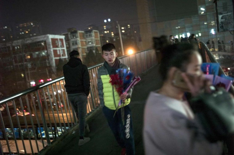 A pedestrian holds flowers as he walks during Valentine's Day on a footbridge in Beijing on February 14, 2017. A Pakistani court has banned public celebrations of Valentine's Day in the capital Islamabad while Indonesian students plan to spurn the event, as the festival of love gets a chilly reception in parts of Asia. (FRED DUFOUR/AFP/Getty Images)