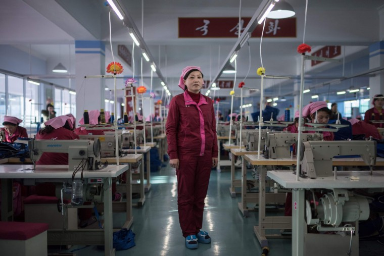 In this photo taken on February 18, 2017, a woman stands between sewing machines at a facility described to AFP as the 'Pyongyang Bag Factory' in Pyongyang. / (AFP Photo/Ed Jones)