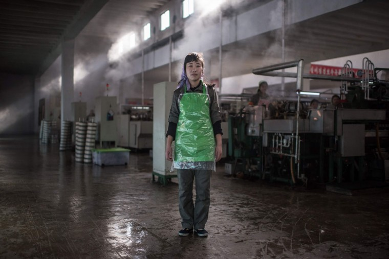 In this photo taken on February 21, 2017, Kim Sun-Ok, 27, poses for a portrait at the Kim Jong-Suk silk mill in Pyongyang. A regular fixture on the itineraries of foreign journalists and tourists, the Kim Jong-Suk silk mill employs a workforce of 1600 and is named after the grandmother of current North Korean leader Kim Jong-Un. / (AFP Photo/Ed Jones)