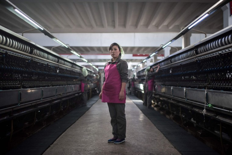 In this photo taken on February 21, 2017, Ri Jong-Sun, 25, poses for a portrait at the Kim Jong-Suk silk mill in Pyongyang. A regular fixture on the itineraries of foreign journalists and tourists, the Kim Jong-Suk silk mill employs a workforce of 1600 and is named after the grandmother of current North Korean leader Kim Jong-Un. / (AFP Photo/Ed Jones)