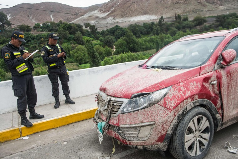 Policemen take notes next to a car at the Peruvian Panamerican highway after a landslide in Arequipa, southern Peru, on January 27, 2017. Floods and landslides in Peru have killed four people and displaced more than 11,000 families over recent weeks, the authorities said Friday. Three people drowned when their vehicle was caught in a flood in the southern Arequipa region, the National Civil Defense Institute said. (Ernesto Benavides/AFP/Getty Images)