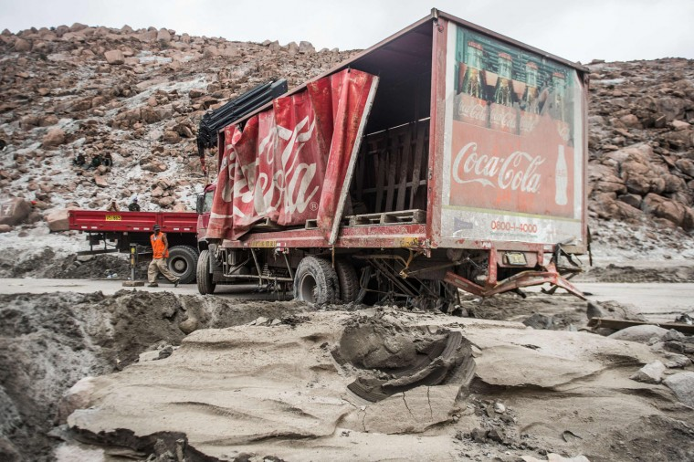 A man walks next to a truck during rescue works at the Peruvian Panamerican highway after a landslide in Arequipa, southern Peru, on January 27, 2017. Floods and landslides in Peru have killed four people and displaced more than 11,000 families over recent weeks, the authorities said Friday. Three people drowned when their vehicle was caught in a flood in the southern Arequipa region, the National Civil Defense Institute said. (Ernesto Benavides/AFP/Getty Images)
