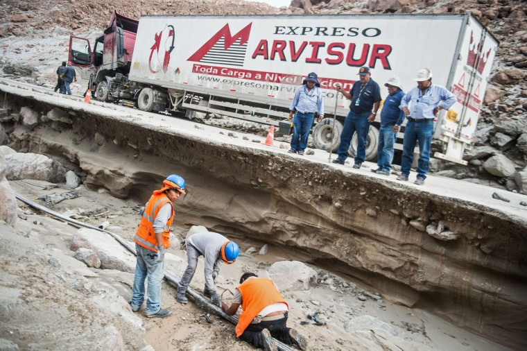 Men take part in rescue works at the Peruvian Panamerican highway after a landslide in Arequipa, southern Peru, on January 27, 2017. Floods and landslides in Peru have killed four people and displaced more than 11,000 families over recent weeks, the authorities said Friday. Three people drowned when their vehicle was caught in a flood in the southern Arequipa region, the National Civil Defense Institute said. (Ernesto Benavides/AFP/Getty Images)