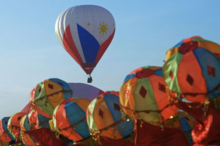 A Hot air balloon in colours of the Philippine flag is seen past dancers wearing balloon-themed outfits during the annual International Hot Air Balloon Festival at the former Clark US Air Force base in Pampanga province, north of Manila on February 9, 2017. Some 29 balloon enthusiasts from around the globe are participating in the event which runs February 9 to 12. (TED ALJIBE/AFP/Getty Images)