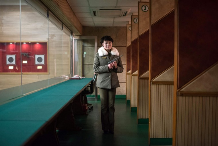 In this photo taken on February 21, 2017, shooting instructor Kim Su-Ryon poses for a portrait at the Meari Shooting Range in Pyongyang.Kim is holding a 'Paektusan' target pistol, gifted by late North Korean leader Kim Il-Sung. Visitors to the range can pay 10 USD to shoot ten rounds. / (AFP Photo/Ed Jones)