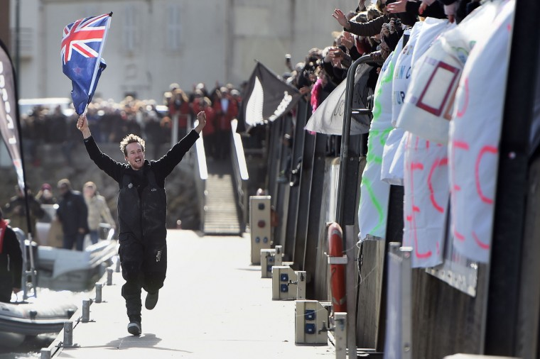 """New Zealand's skipper Conrad Colman, holding a New Zealand national flag, greets supporters after he arrived on his Imoca 60 monohull """"Foresight Natural Energy"""" in Les Sables-d'Olonne, western France, at the end of the Vendee Globe around-the-world solo sailing race on February 24, 2017. Colman finished 16th. (Jean-Sebastien Evrard/AFP/Getty Images)"""