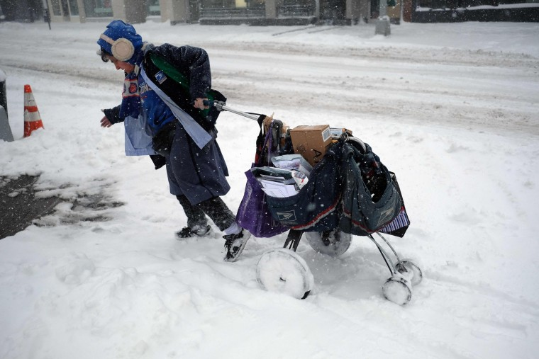 A postwoman drags her mail cart on a snow-covered street during a winter storm in New York on February 9, 2017. A heavy winter snow storm lashed the northeastern United States Thursday, subjecting New York to near blizzard-like conditions and forcing flight cancellations as schools and the United Nations closed. (Jewel Samad/AFP/Getty Images)