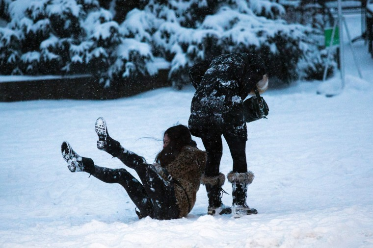 A woman falls down as people walk under a snowfall as they visit Central Park during a winter storm on January 7, 2017 in New York. (Eduardo Munoz Alvarez/AFP/Getty Images)