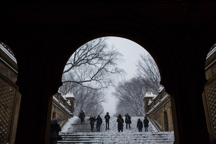 People walk under a snowfall in Central Park during a winter storm on January 7, 2017 in New York. (Eduardo Munoz Alvarez/AFP/Getty Images)