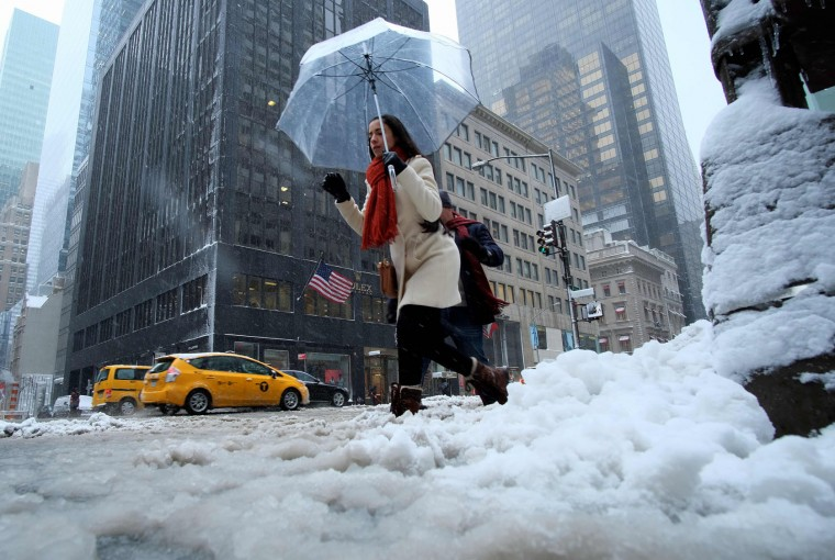 A man shovels snow from a street during a winter storm in New York on February 9, 2017. A heavy winter snow storm lashed the northeastern United States Thursday, subjecting New York to near blizzard-like conditions and forcing flight cancellations as schools and the United Nations closed. (Jewel Samad/AFP/Getty Images)