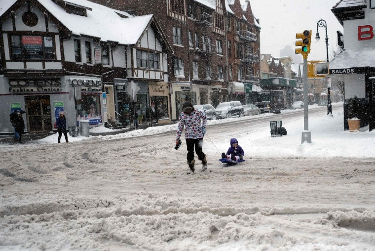A woman pulls a child on a sled as they cross a street during a winter storm in New York on February 9, 2017. A heavy winter snow storm lashed the northeastern United States Thursday, subjecting New York to near blizzard-like conditions and forcing flight cancellations as schools and the United Nations closed. (Jewel Samad/AFP/Getty Images)