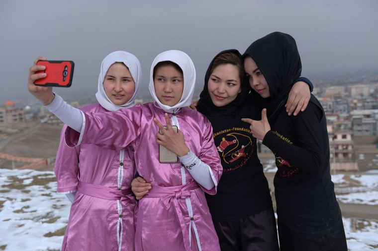In this photograph taken on January 29, 2017, Afghan members of a wushu martial arts group take a 'selfie' after posing for photographs at the Shahrak Haji Nabi hilltop overlooking Kabul. Afghanistan's first female wushu trainer, Sima Azimi, 20, is training 20 Afghan girls aged between 14 - 20 at a wushu club in Kabul, after learning the sport while living as a refugee in Iran.