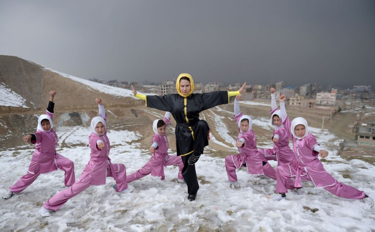 n this photograph taken on January 29, 2017, Afghan members of a wushu martial arts group led by trainer Sima Azimi (C), 20, pose for a photograph at the Shahrak Haji Nabi hilltop overlooking Kabul. Afghanistan's first female wushu trainer, Sima Azimi, 20, is training 20 Afghan girls aged between 14 - 20 at a wushu club in Kabul, after learning the sport while living as a refugee in Iran.