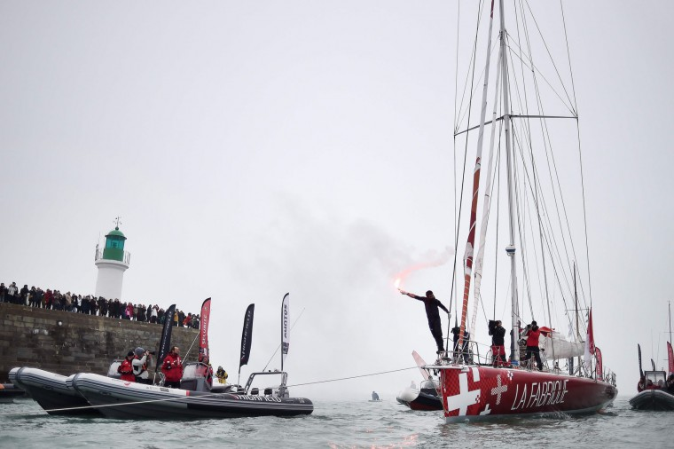 """Swiss skipper Alan Roura, placing 12th in his first participation to the Vendee Globe around-the-world solo sailing race, celebrates aboard his Imoca 60 monohull """"La Fabrique"""" on February 20, 2017 as he arrives in Les Sables-d'Olonne, western France. (Jean-Sebastien Evrard/AFP/Getty Images)"""