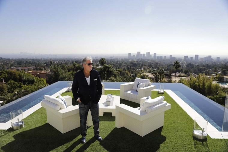 In this Thursday, Jan. 26, 2017, photo, developer Bruce Makowsky poses for a photo on the balcony off the master bedroom of a $250 million mansion he built in the Bel-Air area of Los Angeles. The mansion, the most expensive home listed in the U.S., includes 12 bedroom suites, 21 bathrooms, five bars, three gourmet kitchens, a spa and an 85-foot infinity swimming pool with stunning views of Los Angeles. (AP Photo/Jae C. Hong)