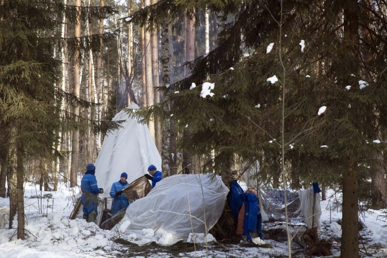 NASA astronaut Andrew J. Feustel, center, and Russian Cosmonauts Oleg Artemyev, left, and Sergej Prokopyev attend a three-day winter training session in a forest at Russian Space Training Center in Star City, outside Moscow, Russia, Wednesday, Feb. 8, 2017. The three are being trained for a future mission to the International Space Station. (AP Photo/Pavel Golovkin)