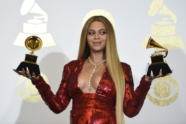 """Beyonce poses in the press room with the awards for best music video for """"Formation"""" and best urban contemporary album for """"Lemonade"""" at the 59th annual Grammy Awards at the Staples Center on Sunday, Feb. 12, 2017, in Los Angeles. (Photo by Chris Pizzello/Invision/AP)"""
