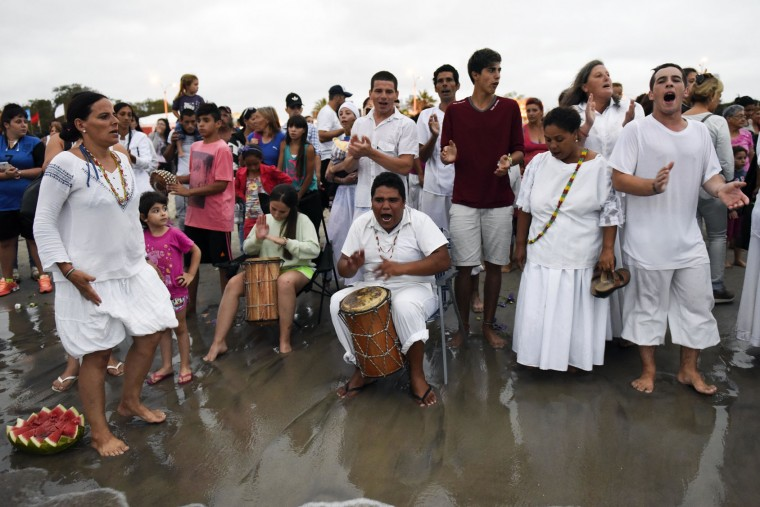 Worshippers sing to honor the African sea goddess Yemanja, at the sea shore in Montevideo, Uruguay, Thursday, Feb. 2, 2017. Thousands of worshippers come to the beach on Yemanja's feast day, bearing candles, flowers, perfumes and fruit to show their gratitude for her blessings. The celebration coincides with the Roman Catholic feast day of the Virgin of Candelaria, marked Feb. 2. (AP Photo/Matilde Campodonico)