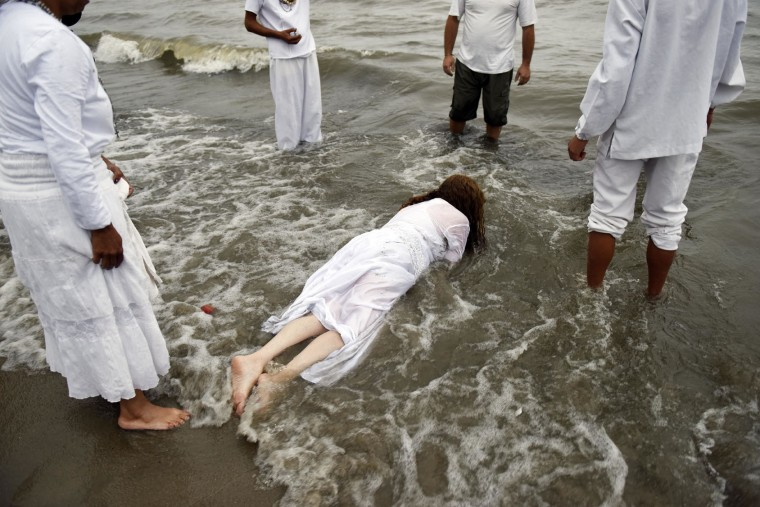 A woman lies face down in the water during a ritual honoring the African sea goddess Yemanja, in Montevideo, Uruguay, Thursday, Feb. 2, 2017. Thousands of worshippers come to the beach on Yemanja's feast day, bearing candles, flowers, perfumes and fruit to show their gratitude for her blessings. The celebration coincides with the Roman Catholic feast day of the Virgin of Candelaria, marked Feb. 2. (AP Photo/Matilde Campodonico)