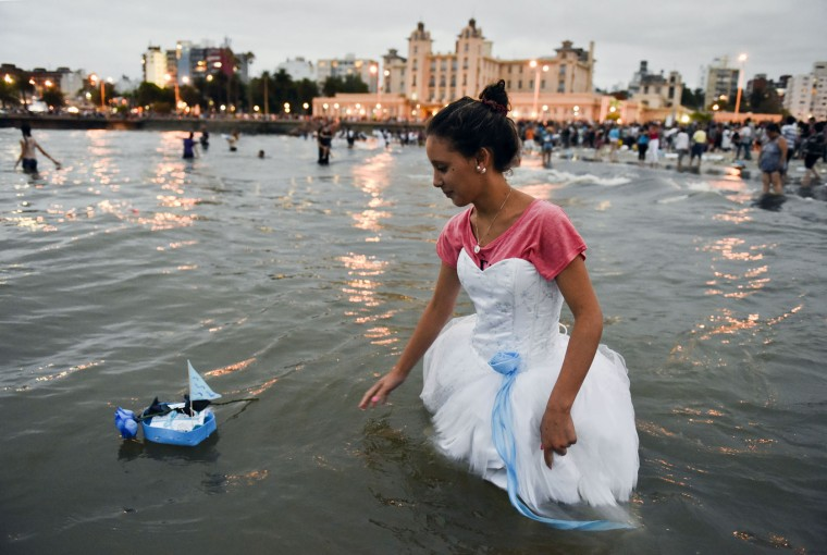 A woman releases a small boat as an offering for the African sea goddess Yemanja, at a beach in Montevideo, Uruguay, Thursday, Feb. 2, 2017. Thousands of worshippers come to the beach on Yemanja's feast day, bearing candles, flowers, perfumes and fruit to show their gratitude for her blessings. The celebration coincides with the Roman Catholic feast day of the Virgin of Candelaria, marked Feb. 2. (AP Photo/Matilde Campodonico)