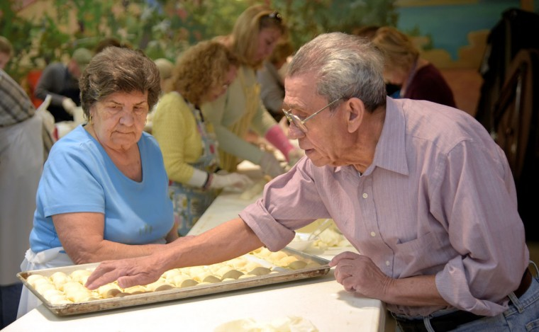 Teresa Corapi, 80 watches as Vincenzo Mirarchi, 79, counts the raviolis on the tray before he carries it to the next station. There should be sixty. (Algerina Perna/Baltimore Sun)