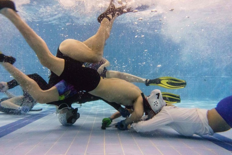 "In this photo taken on February 15, 2017, members of the ""HK Typhoon"" underwater hockey club fight for possession of the puck during their once-a-week team practice session at a 25-meter school pool in Hong Kong. The gravity defying sport of underwater hockey has gained a worldwide following -- now a Hong Kong team is diving in as the game takes off in Asia. (ANTHONY WALLACE/AFP/Getty Images)"