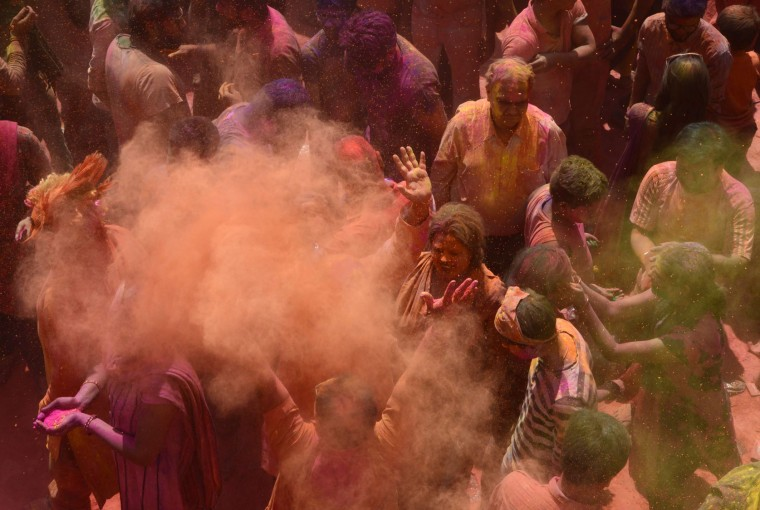 Indian Hindu devotees take part in celebrations for the Holi festival at a Temple in Siliguri on March 13, 2017. Holi marks the welcoming of spring and is a celebration of the triumph of good over evil, with people chasing each other and playfully splashing colorful paint, powder and water on each other. (Diptendu Dutta/AFP/Getty Images)