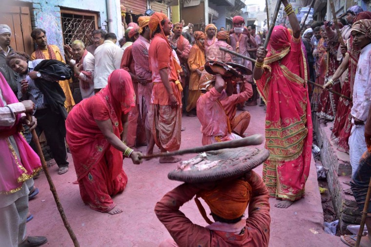 "In this photograph taken on March 6, 2017, Indian women beat men with sticks (Lathi) during celebrations for Lathmar Holi in Barsana on the outskirts of Mathura in the northern Indian state of Uttar Pradesh. Lathmar Holi is a local celebration of the Hindu festival of Holi, usually some days ahead of the actual festival - it translates as 'that Holi in which people hit with sticks"". (STRSTR/AFP/Getty Images)"