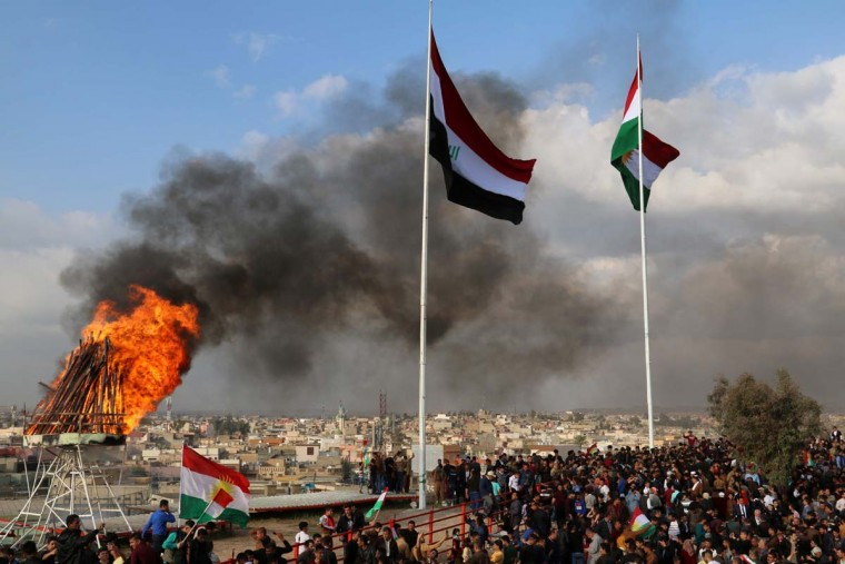 The Kurdish and Iraqi flag sway in the wind as a bonfire burns during the Noruz spring festival celebrations in the northern city of Kirkuk, about 240 kilometers (150 miles) north of Baghdad on March 20, 2017. (MARWAN IBRAHIM/AFP/Getty Images)