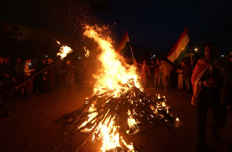 Iraqi Kurds stand around a fire in the Kurdish town of Akra, 500 km north of Baghdad, on March 20, 2017, as they celebrate the Noruz spring festival. (SAFIN HAMED/AFP/Getty Images)