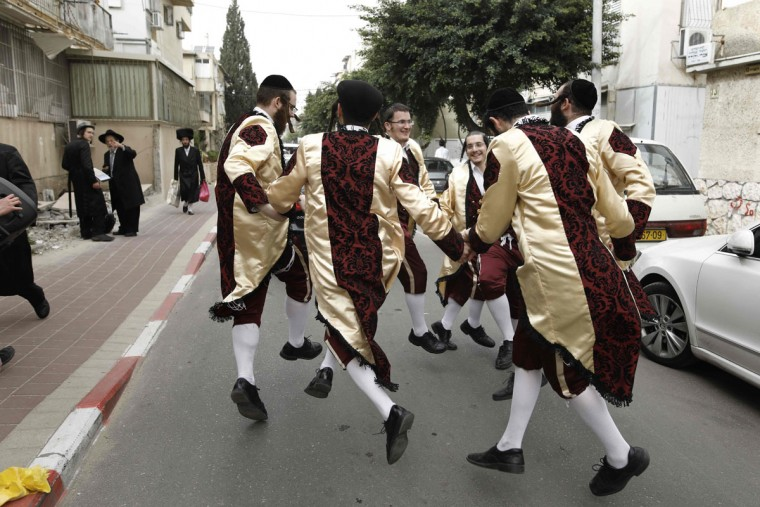 Ultra-Orthodox Jewish men wearing costumes dance on a street in the central Israeli city of Bnei Brak on March 12, 2017 during the feast of Purim. The carnival-like Purim holiday is celebrated with parades and costume parties to commemorate the deliverance of the Jewish people from a plot to exterminate them in the ancient Persian Empire 2,500 years ago, as recorded in the Biblical Book of Esther. (AFP PHOTO / MENAHEM KAHANA)