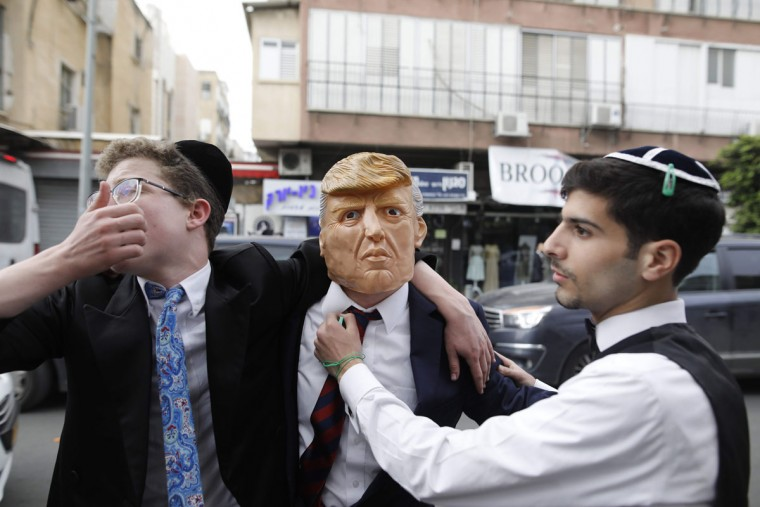 An ultra-Orthodox Jewish man wears a mask of the US President Donald Trump in the central Israeli city of Bnei Brak on March 12, 2017 during the feast of Purim. The carnival-like Purim holiday is celebrated with parades and costume parties to commemorate the deliverance of the Jewish people from a plot to exterminate them in the ancient Persian Empire 2,500 years ago, as recorded in the Biblical Book of Esther. (AFP PHOTO / MENAHEM KAHANA)