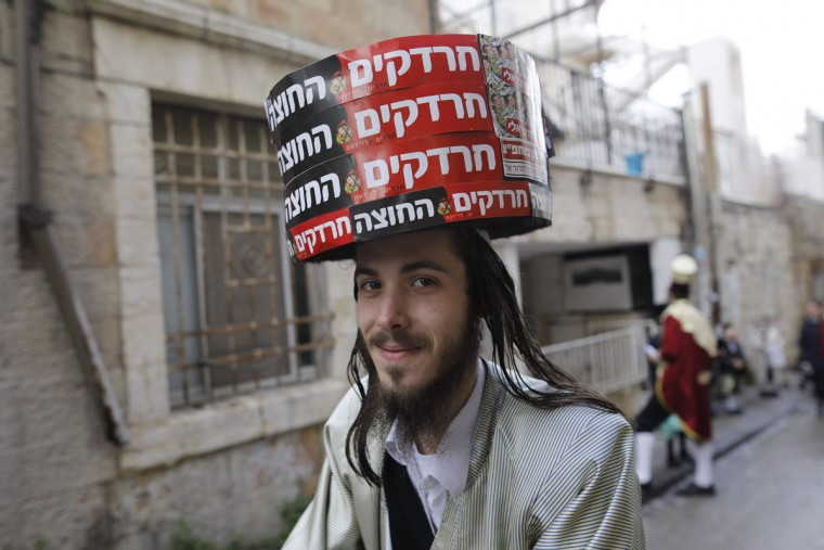 An ultra-Orthodox Jewish man wearing a costume bearing anti-Israeli slogans walk in Jerusalem's Mea Shearim ultra-Orthodox neighbourhood on March 13, 2017 during the religious holiday of Purim. The carnival-like Purim holiday is celebrated with parades and costume parties to commemorate the deliverance of the Jewish people from a plot to exterminate them in the ancient Persian Empire 2,500 years ago, as recorded in the Biblical Book of Esther. (AFP PHOTO / MENAHEM KAHANA)