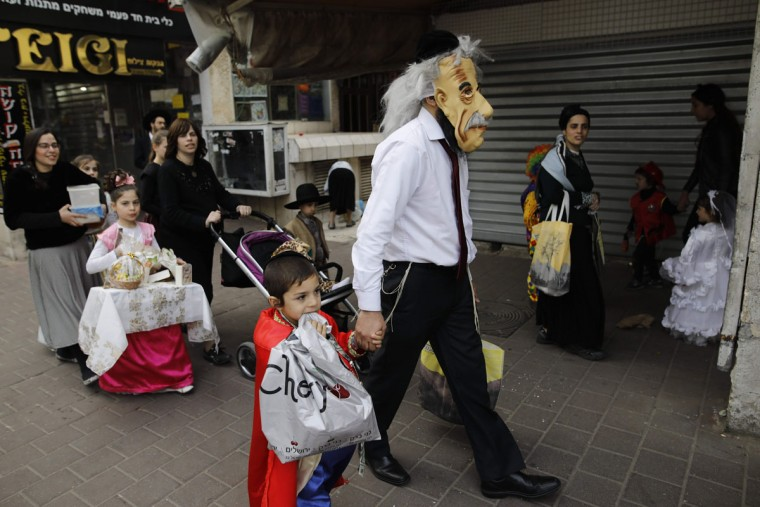An ultra-Orthodox Jewish family wearing costumes walks in the central Israeli city of Bnei Brak on March 12, 2017 during the feast of Purim. The carnival-like Purim holiday is celebrated with parades and costume parties to commemorate the deliverance of the Jewish people from a plot to exterminate them in the ancient Persian Empire 2,500 years ago, as recorded in the Biblical Book of Esther. (AFP PHOTO / MENAHEM KAHANA)