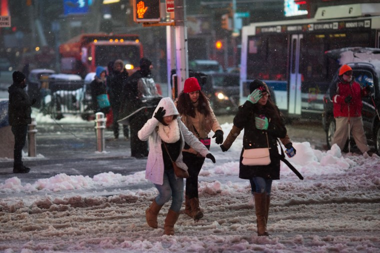 Tourists cross the street in Times Square during a day of heavy snow and freezing rain on March 14, 2017 in New York City. Much of the Northeast is under a state of emergency as a blizzard is expected to bring over one foot of snow and high winds to the area. (Photo by Kevin Hagen/Getty Images)