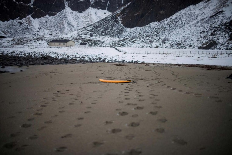A surfboard is left on the sandy beach at Unstad along the northern Atlantic Ocean on March 12, 2017. (OLIVIER MORIN/AFP/Getty Images)