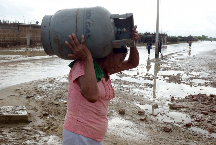 A local resident carries a gas cylinder through a flooded street after heavy rains in Piura, northern Peru on March 28, 2017. (MIGUEL ARREATEGUI,STR/AFP/Getty Images)