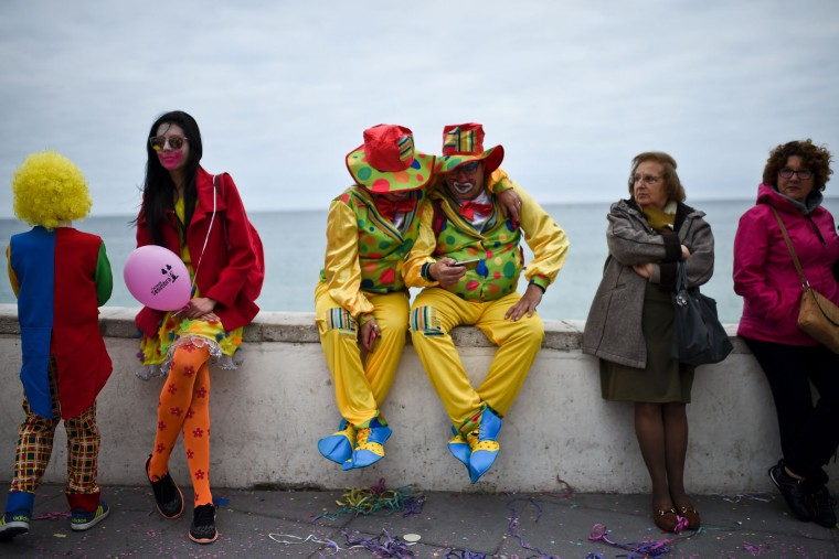 A couple dressed as clowns sit near the beach during the Carnival Clown's Parade at Sesimbra village on February 27, 2017. (Patricia de Melo Moreira/AFP/Getty Images)