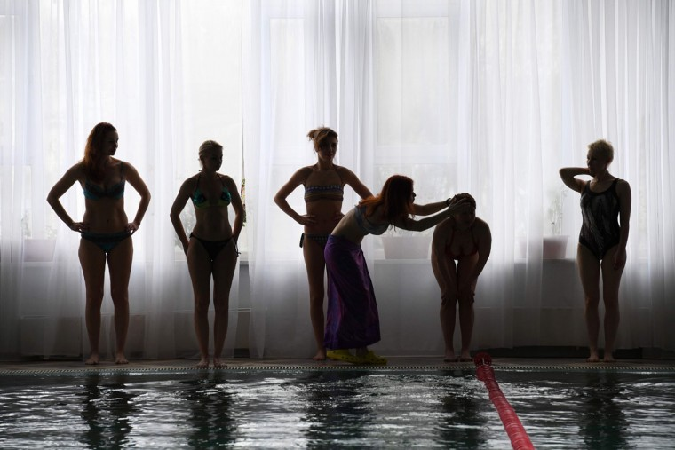 A picture taken on March 16, 2017 shows women warming up ahead of their mermaid class at a pool in Moscow. Russian women who have dreamt of becoming a mermaid since their youngest years, start turning their fantasies into reality with a new type of fitness mermaid swimming. (NATALIA KOLESNIKOVA/AFP/Getty Images)